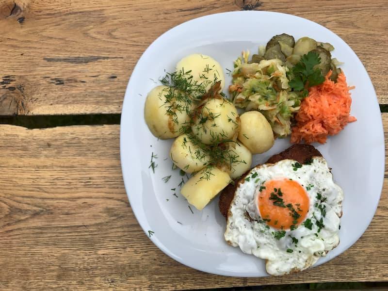 Kotlet mielony okryty sadzonym jajkiem z ziemniakami i zestawem surówek